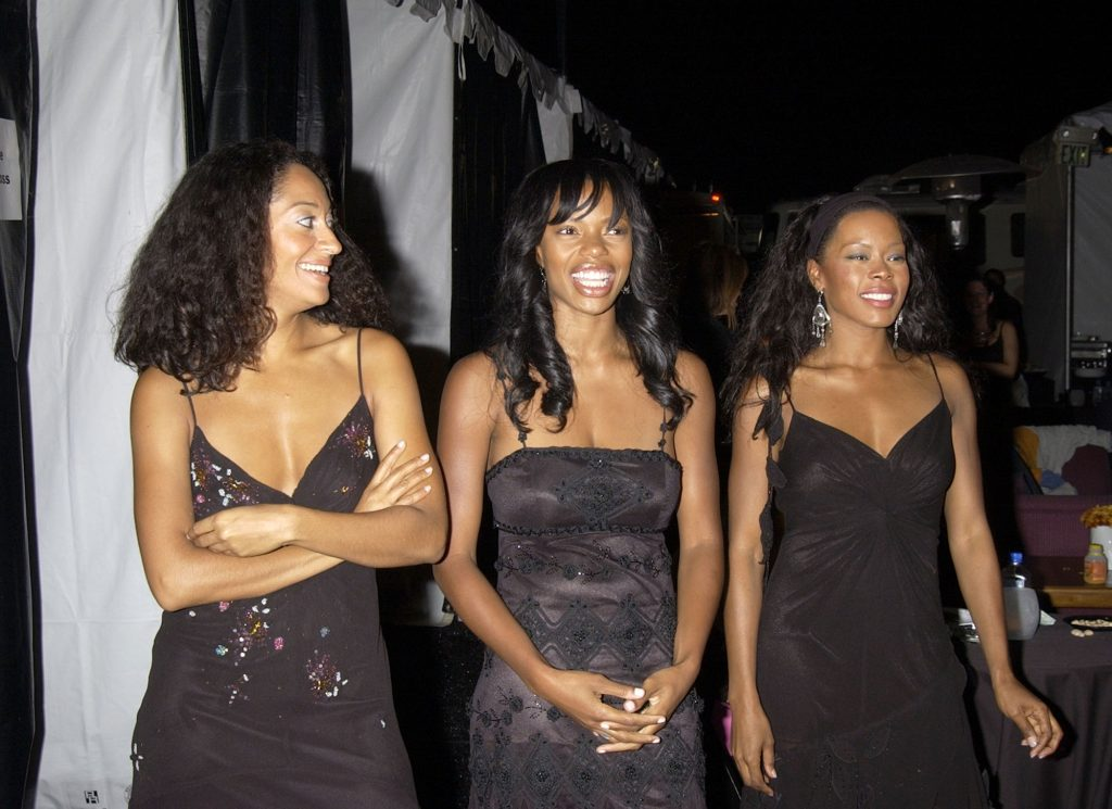 Tracee Ellis Ross, Jill Jones and Golden Brooks smiling in front of a black and white striped background