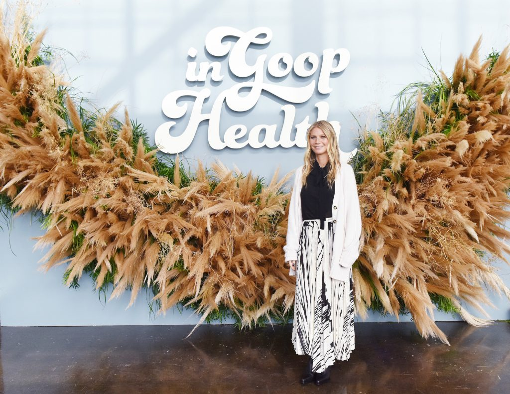 Gwyneth Paltrow smiling in front of a giant wreath