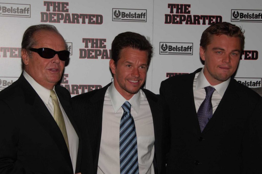 (L-R) Jack Nicholson, Mark Wahlberg, and Leonardo DiCaprio smiling in front of a white background