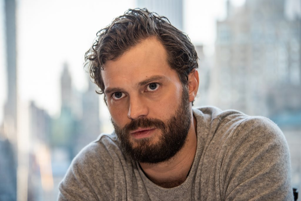 Jamie Dornan in front of a blurred background