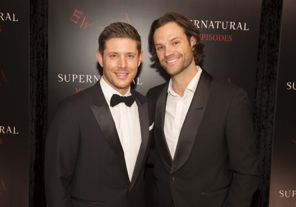 (L-R) Jensen Ackles and Jared Padalecki smiling in front of a black background