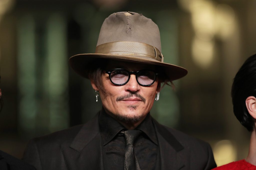 Johnny Depp in a hat and glasses in front of a blurred background