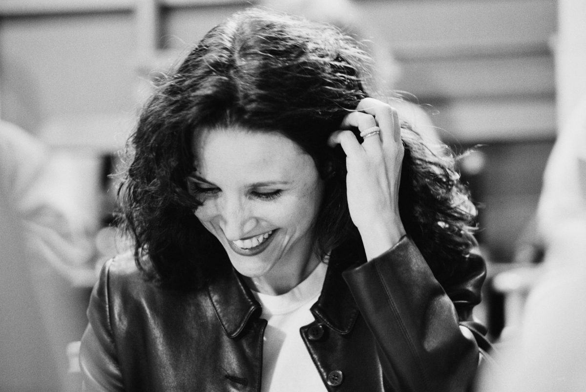 Julia Louis-Dreyfus smiles as she reads a script for 'Seinfeld'