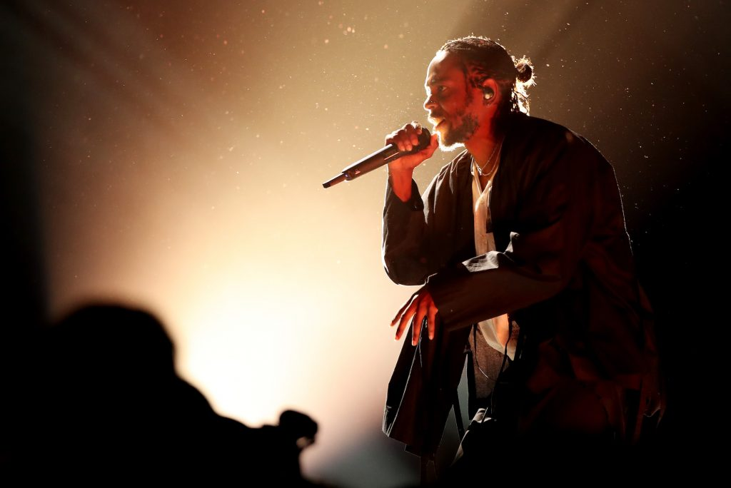 Kendrick Lamar singing into a microphone, photographed from the side