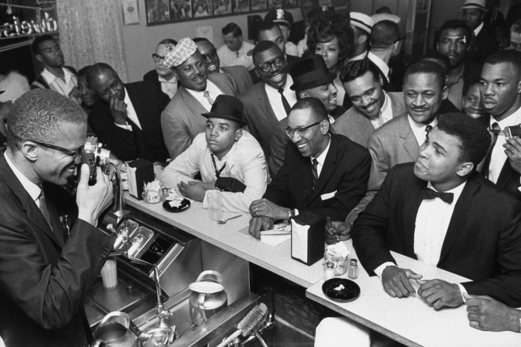 MARCH 1964 - MIAMI: Black Muslim leader Malcolm X (L) behind soda fountain training his camera on tux-clad Cassius Clay (now Muhammad Ali) (R) sitting at counter surrounded by jubilant fans after he beat Sonny Liston for the heavyweight championship of the world.