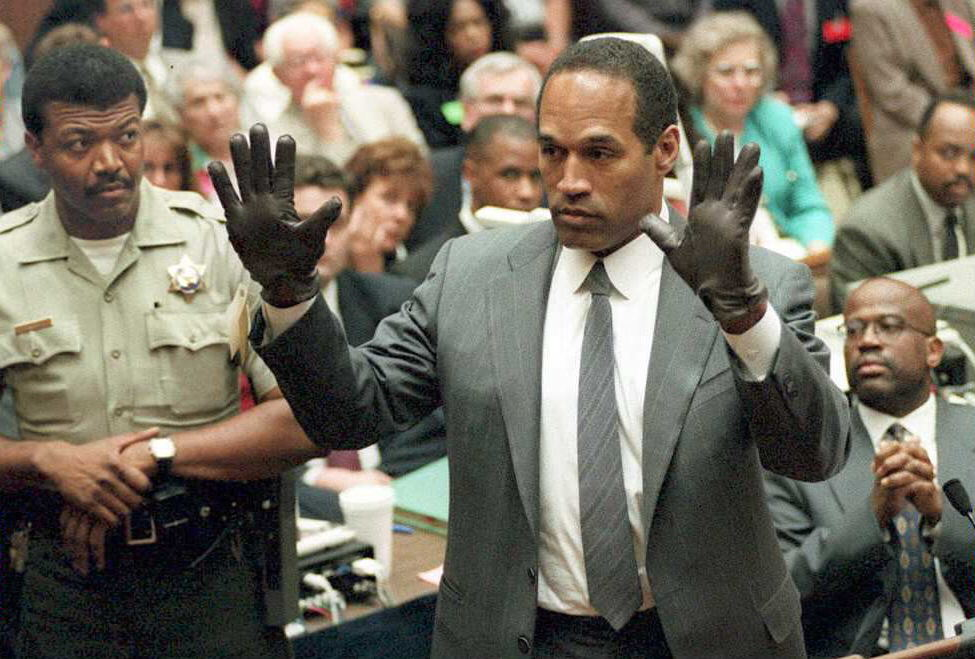 O.J. Simpson holding his hands up, wearing gloves in court