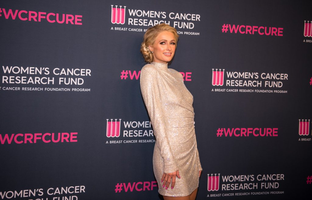 Paris Hilton smiling in front of a dark background with pink logos