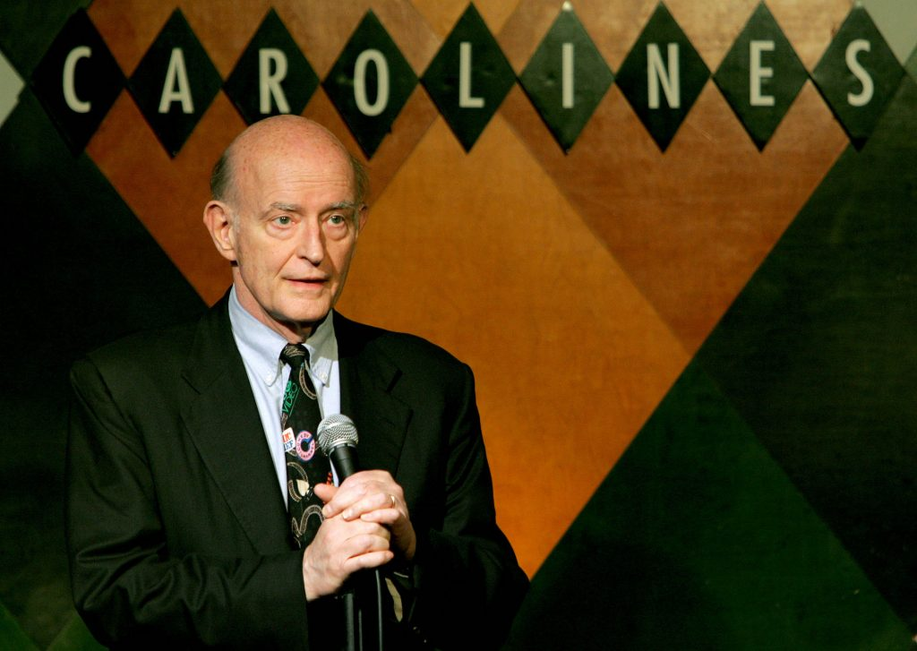 Peter Boyle performing standup, holding a microphone