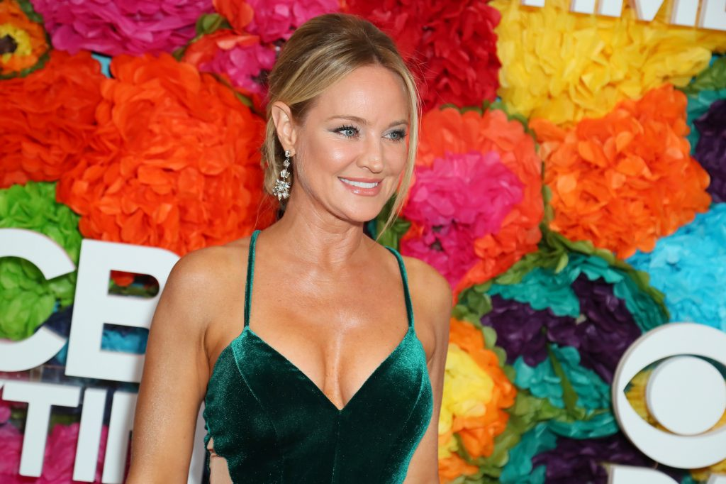 Sharon Case smiling in front of a multi colored background