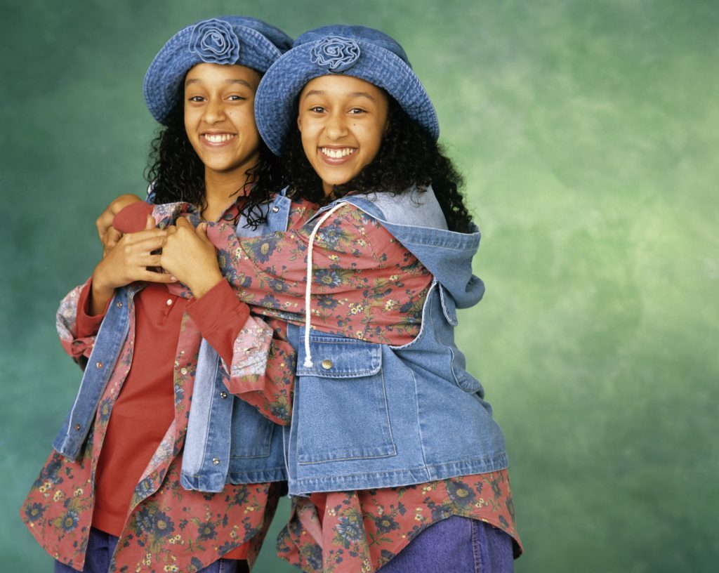 (L-R) Tia Mowry and Tamera Mowry smiling in front of a green background