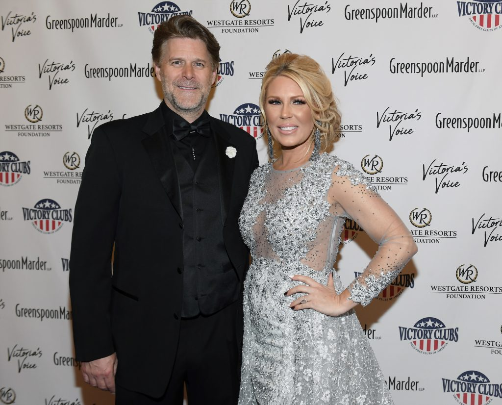 (L-R) Slade Smiley and Gretchen Rossi smiling in front of a white background with repeating text