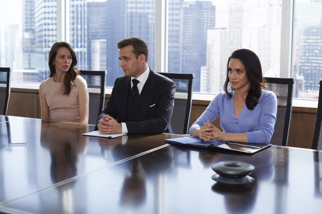 (L-R) Amy Acker as Esther, Gabriel Mact as Harvey Specter, Meghan Markle as Rachel Zane seated at a table on 'Suits'