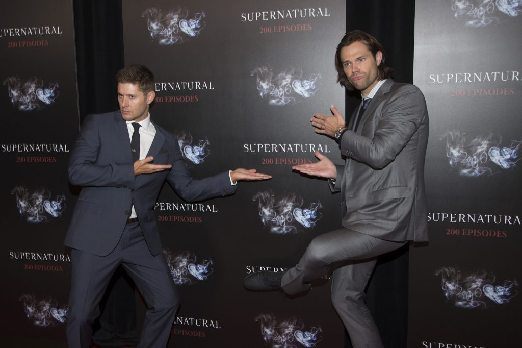 Jensen Ackles and Jared Padalecki striking a silly pose in front of a black background