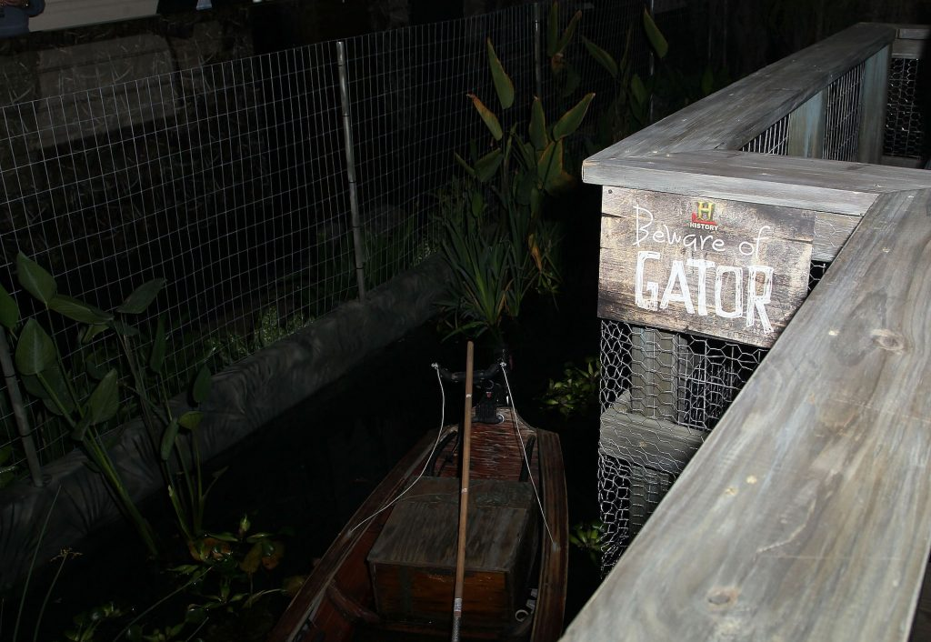 A staged 'swamp' with a boat in it, under a sign saying 'Beware of Gator'