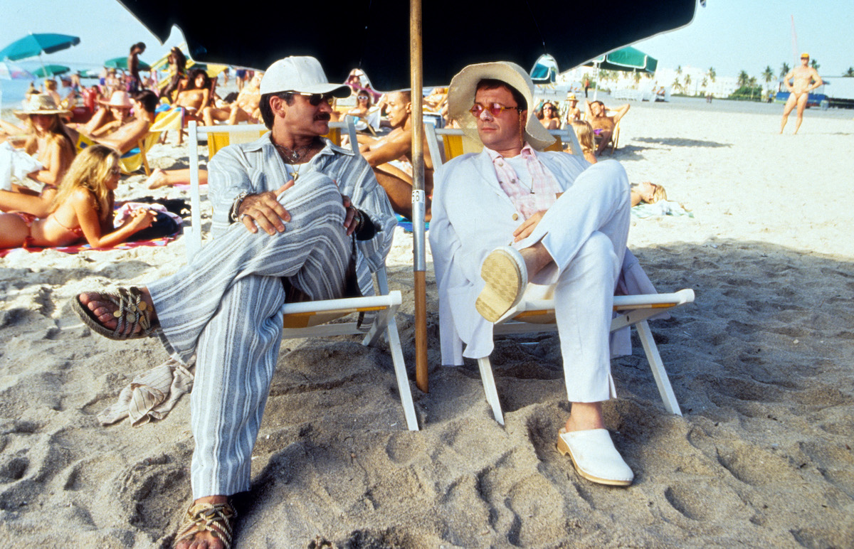 Robin Williams and Nathan Lane sitting under an umbrella on the sand at the beach in a scene from the film 'The Birdcage', 1996