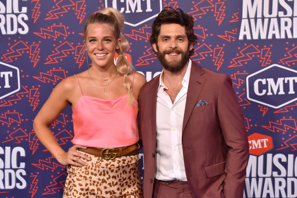 (L-R) Laura Atkins and Thomas Rhett smiling in front of a blue background