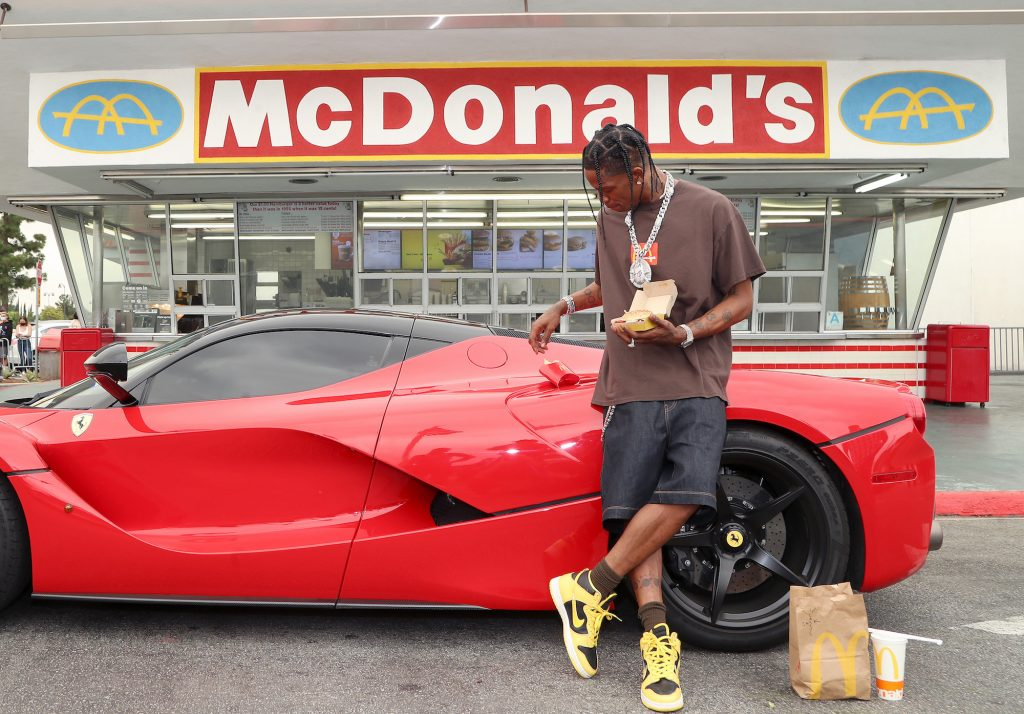Travis Scott leaning against a red car in front of a McDonald's