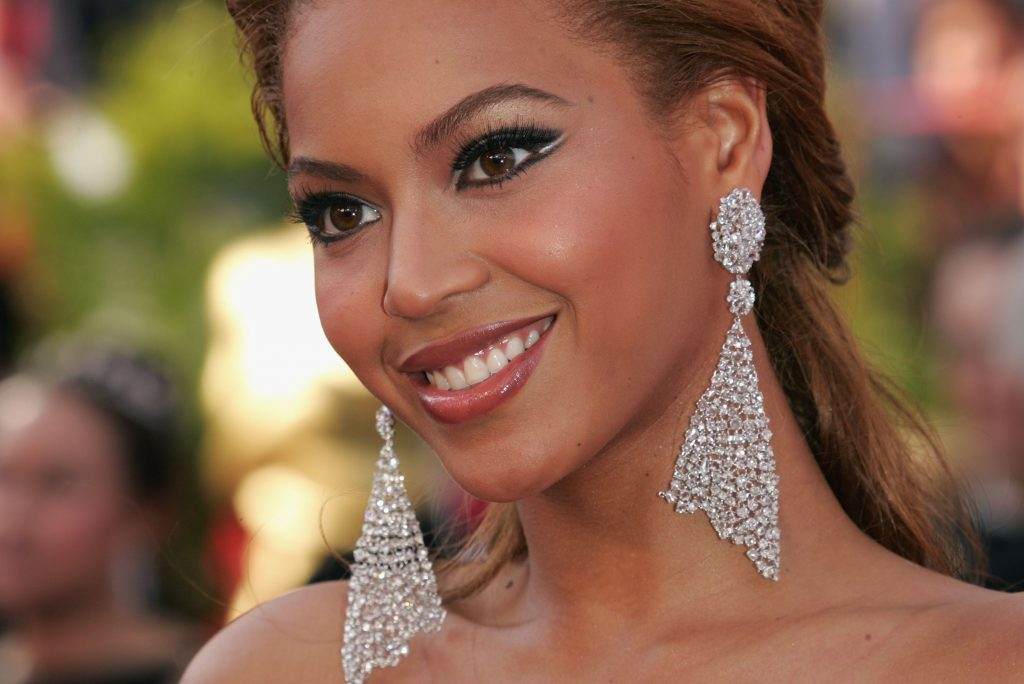 Beyoncé wearing earrings in front of a blurry green background