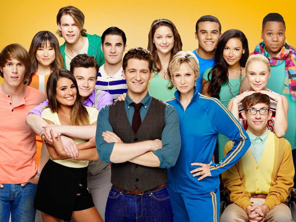 The cast of Glee in front of a yellow background