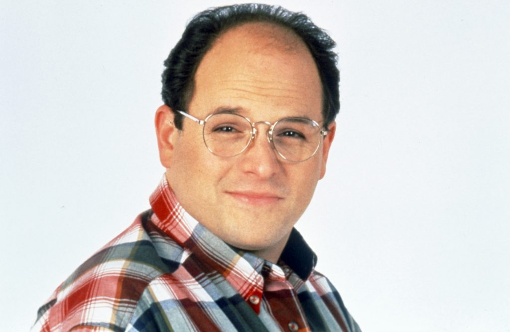 Jason Alexander wearing glasses and a collared shirt while portraying George Costanza