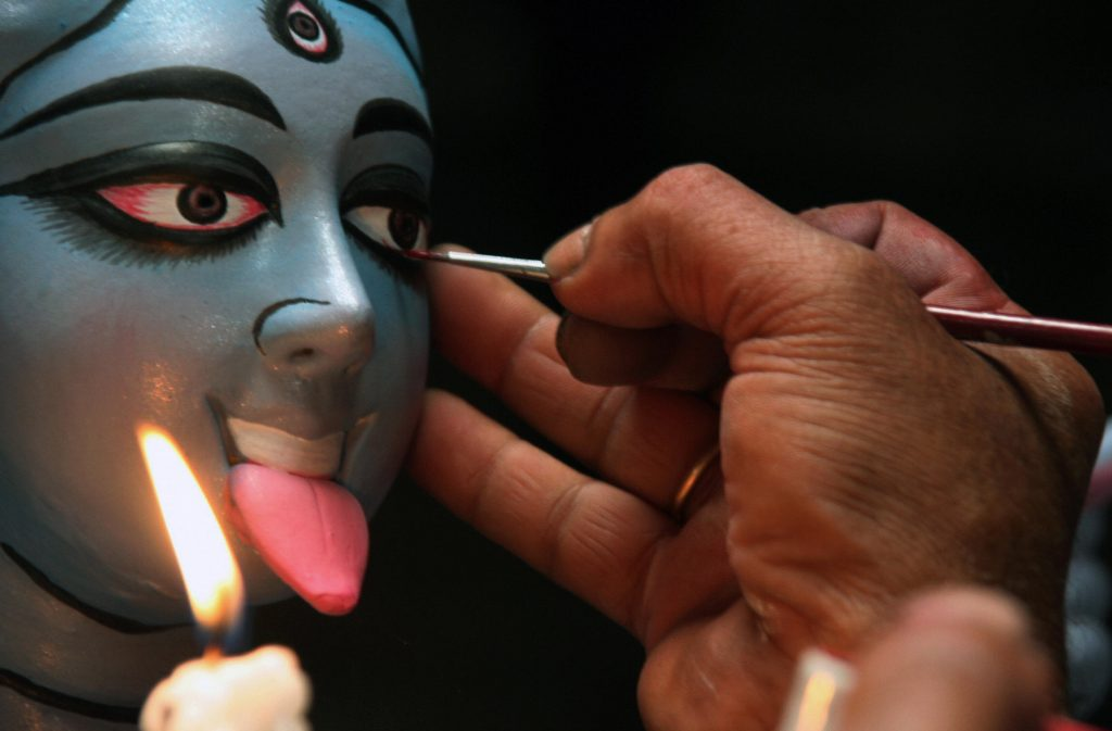 Someone painting an idol of Kali