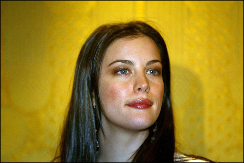 Liv Tyler in front of a yellow background