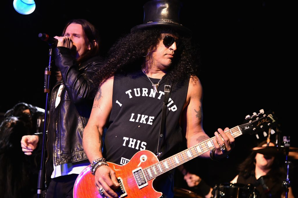 Myles Kennedy singing into a microphone next to Slash with a guitar