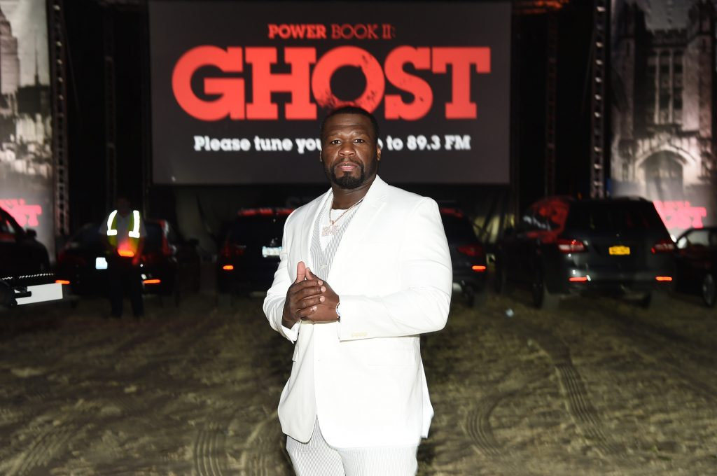 50 Cent holding his hands together in front of a screen with red lettering