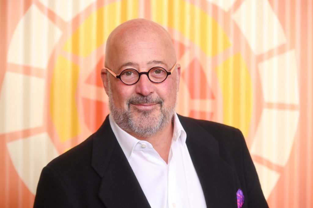 Andrew Zimmern smiling in front of an orange background