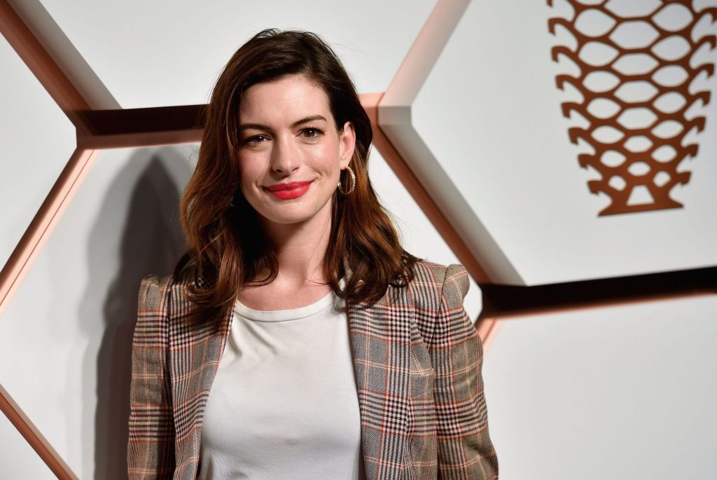 Anne Hathaway smiling in front of a geometric background