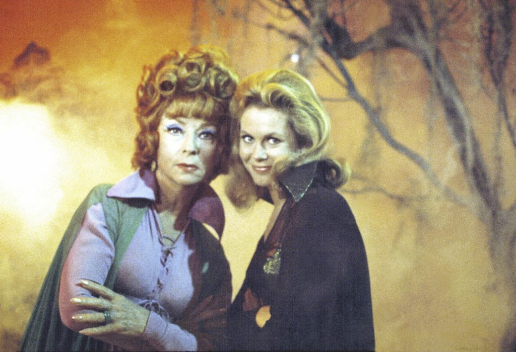 (L-R) Agnes Moorehead as Endora and Elizabeth Montgomery as Samantha Stephens smiling, wearing capes, in front of an orange-lit forest