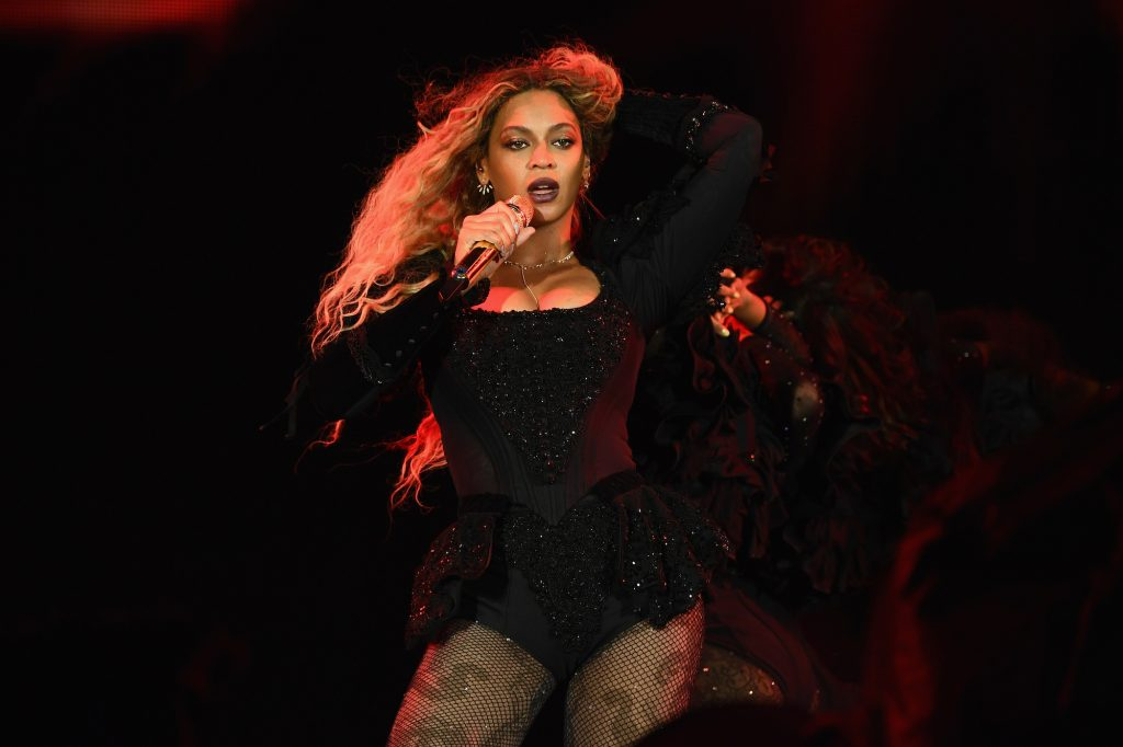 Beyoncé performing onstage, holding a microphone in one hand and adjusting her hair with the other