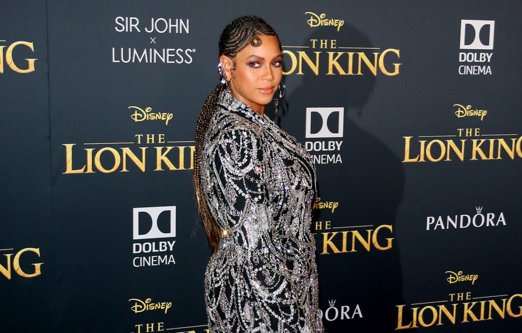 Beyoncé slightly smiling, looking back, in front of a black background with the 'Lion King' logo
