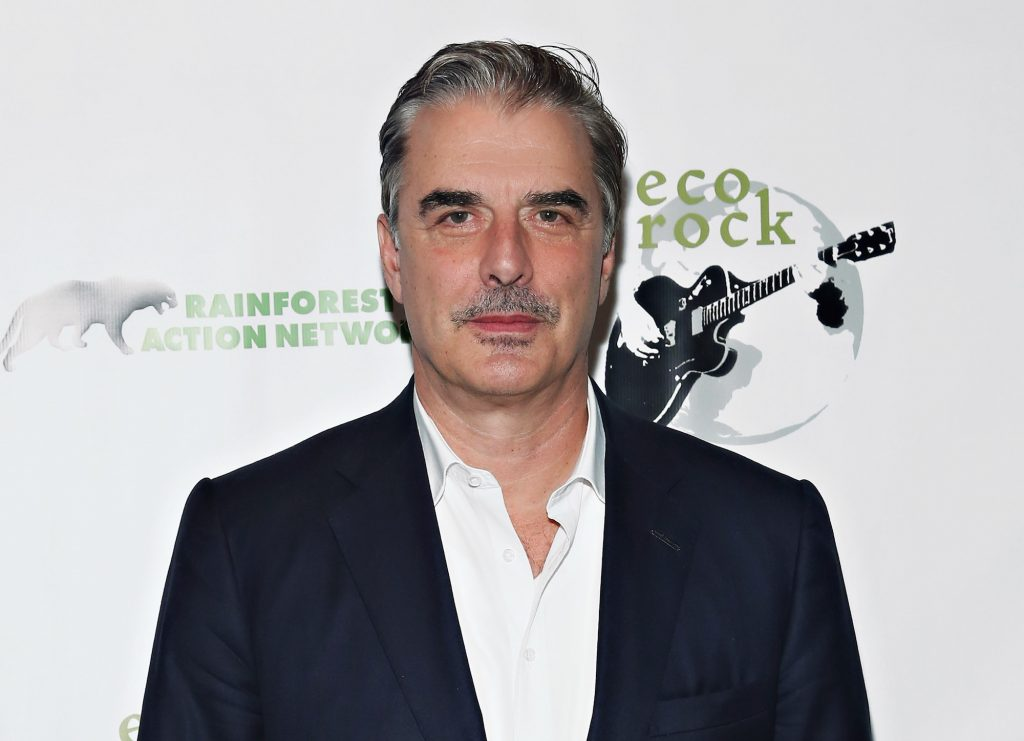 Chris Noth smiling in front of a white background
