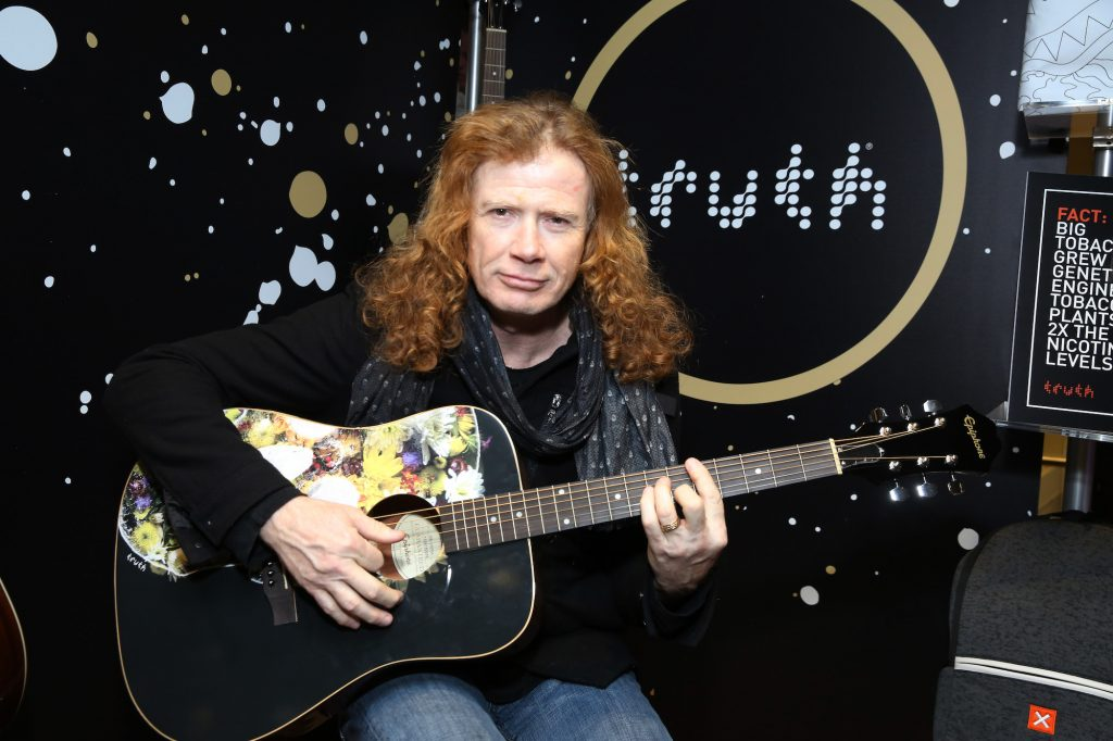 Dave Mustaine slightly smiling, holding a guitar