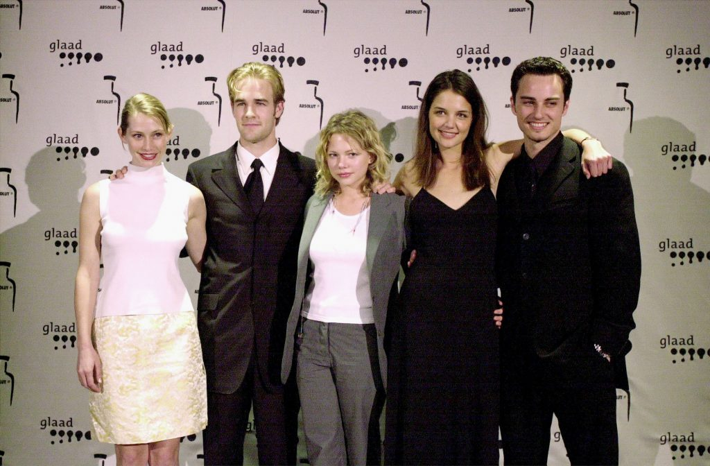 (L-R) Meredith Monroe, James Van der Beek, Michelle Williams, Katie Holmes, and Kerr Smith smiling in front of a white backgrounf