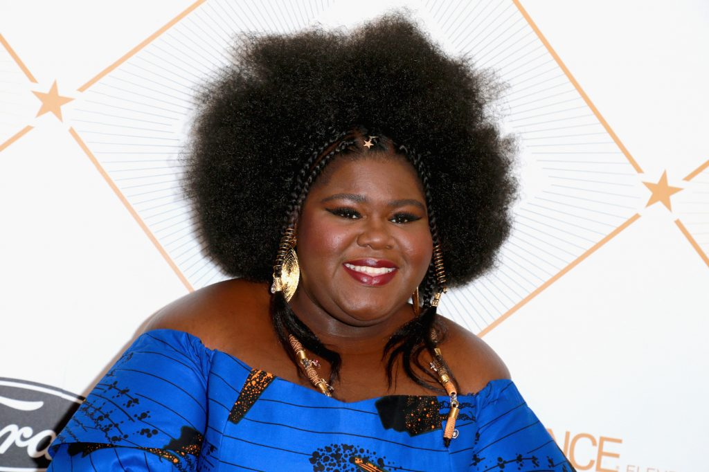 Gabourey Sidibe smiling in front of a white background