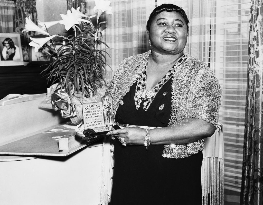 American actress Hattie McDaniel with her Academy Award of Merit for Outstanding Achievement, circa 1945. McDaniel won an Oscar for Best Supporting Actress for her role of Mammy in Gone With The Wind, making her the first African-American to win an Academy Award