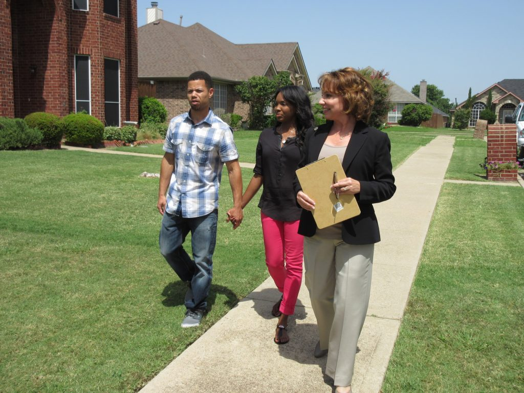 A young couple holding hands walking down a sidewalk with a realtor on 'House Hunters'