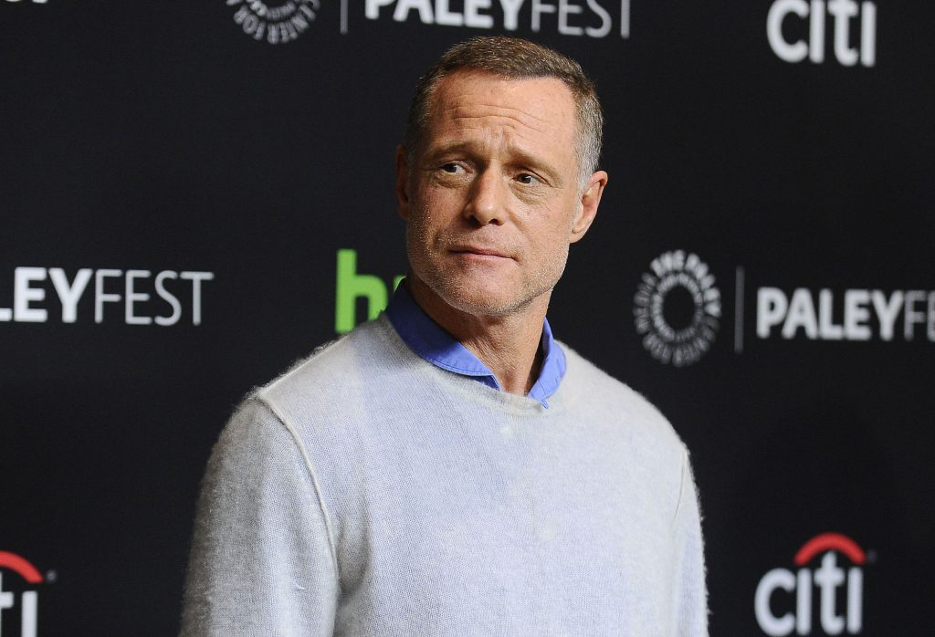 Jason Beghe slightly smiling, looking off to the side, in front of a black background