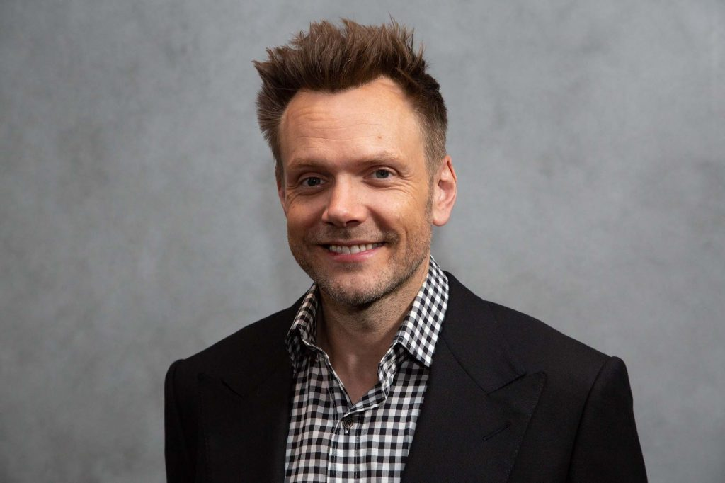 Joel McHale smiling in front of a gray background