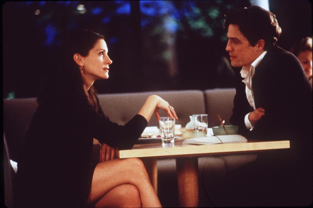 (L-R) Julia Roberts and Hugh Grant in 'Notting Hill' sitting at a dinner table