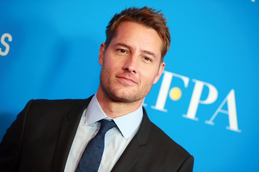 Justin Hartley smiling in front of a blue background