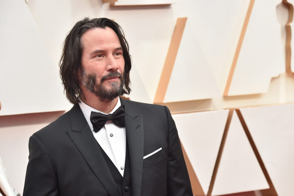 Keanu Reeves smiling, turned away from the camera