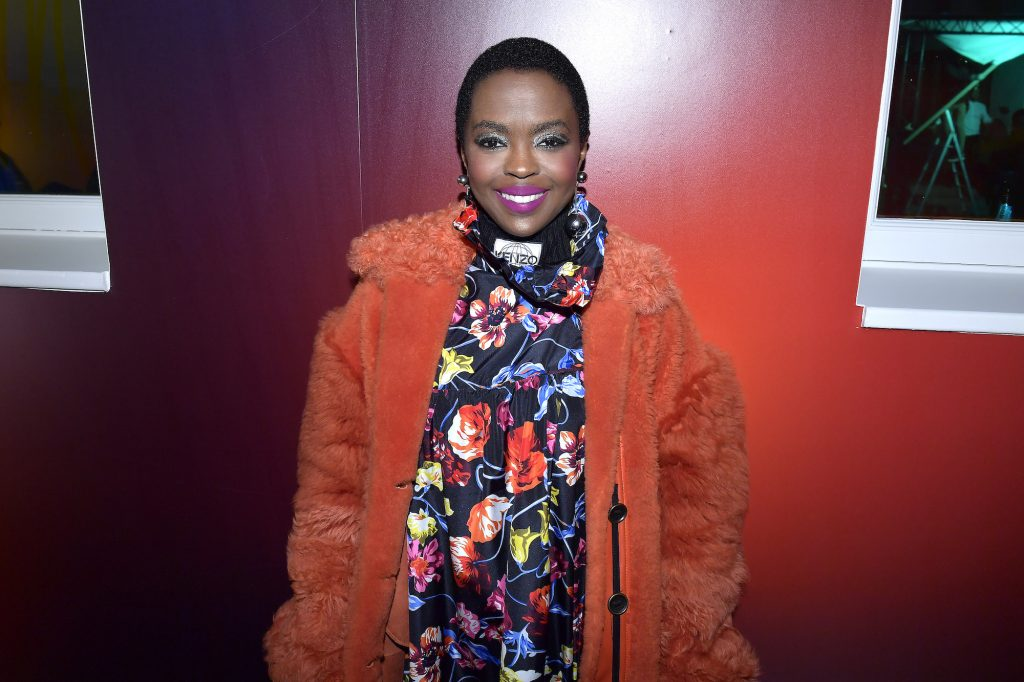 Lauryn Hill smiling in front of a red wall