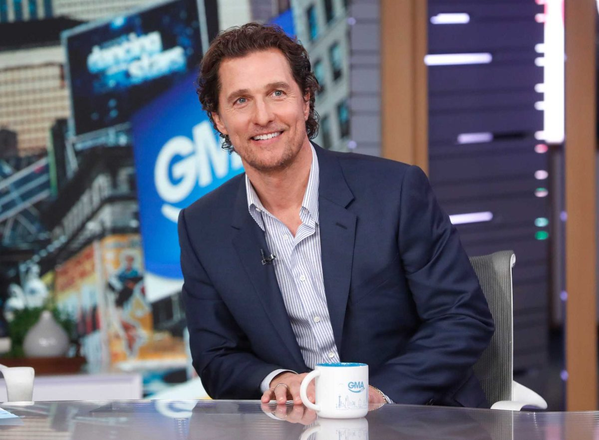 Matthew McConaughey in a dark blazer at a table with a cup