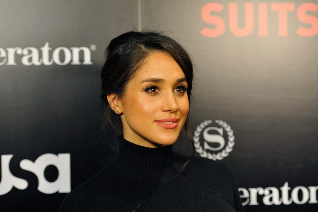 Meghan Markle smiling slightly in front of a black background