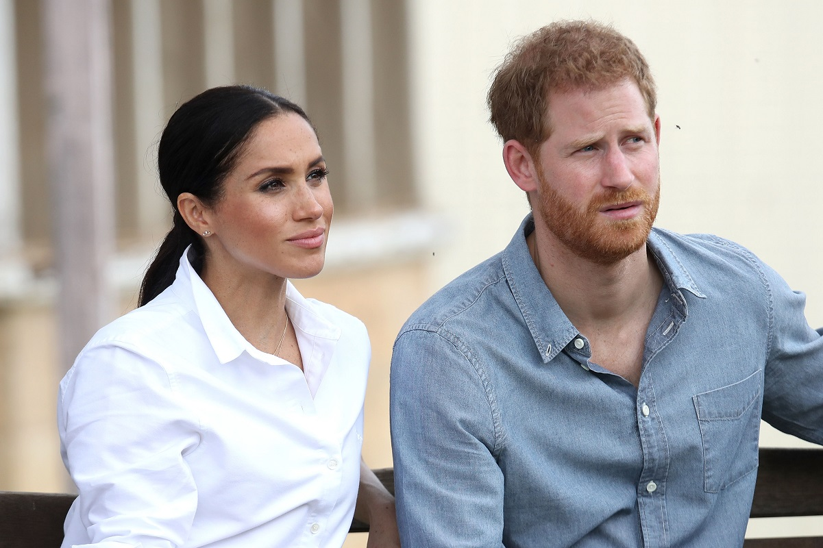 Meghan Markle and Prince Harry sit next to each other and look on