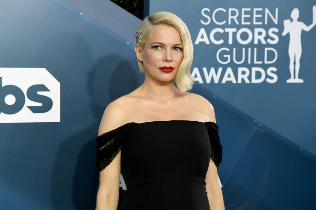 Michelle Williams slightly smiling in front of a blue background