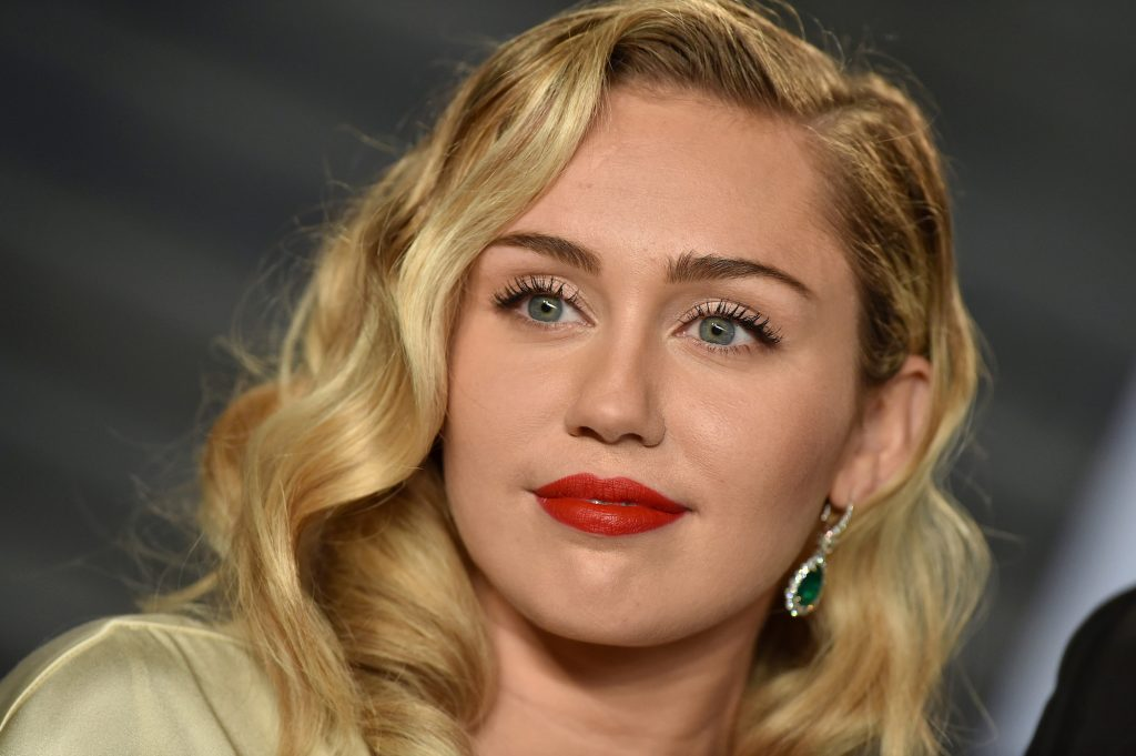 Miley Cyrus slightly smiling, wearing red lipstick, in front of a blurred background